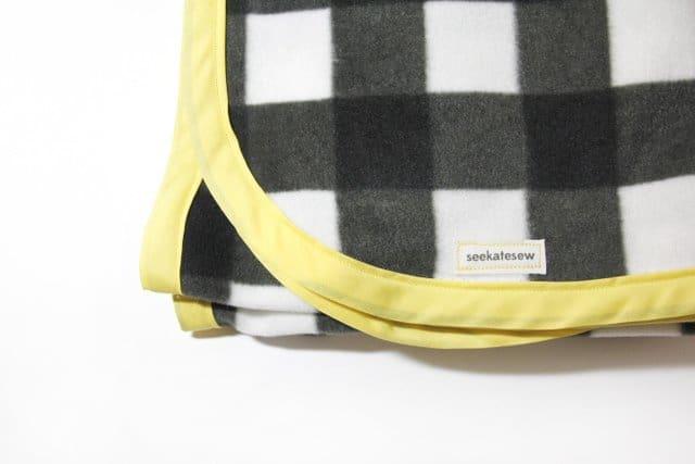 http://seekatesew.com/easy-fleece-bias-tape-blanket-tutorial-with-rounded-corners/