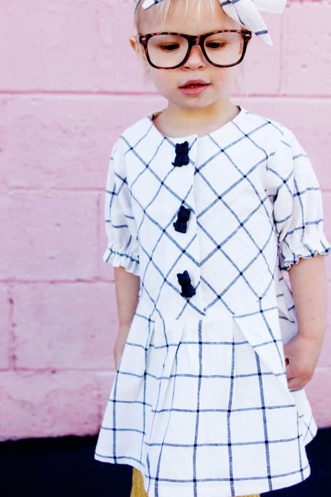 Zig Zag Dress pattern gives a preppy look with it's plaid and pleats! It's curved bodice gives it a really cute swing! Elastic sleeves, big buttons, and facing on the inside makes this dress a dress to love! || See Kate Sew #dresspatterns #kidsfashion #dresses #seekatesew